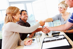 Multiracial business group shaking hands in meeting